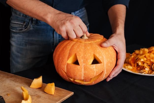 Mann macht einen orangefarbenen kürbis für halloween