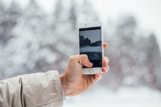 Mann macht foto des schneewinter auf smartphone