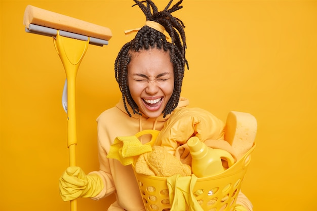 Mann macht hausarbeiten hält mop zum waschen des bodens im haus trägt einen korb mit wäschekorb mit reinigungsmitteln isoliert auf gelb