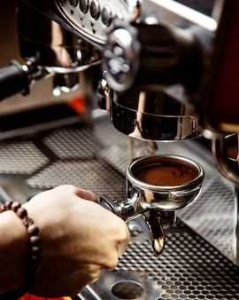 Mann macht kaffee in einer kaffeemaschine