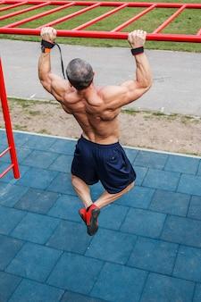 Mann macht klimmzüge am reck