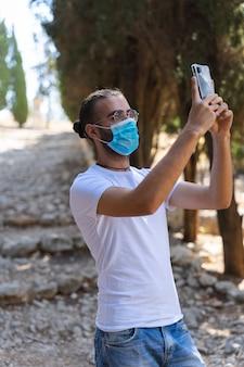 Mann macht mit seinem handy ein foto mit maske und weißem t-shirt
