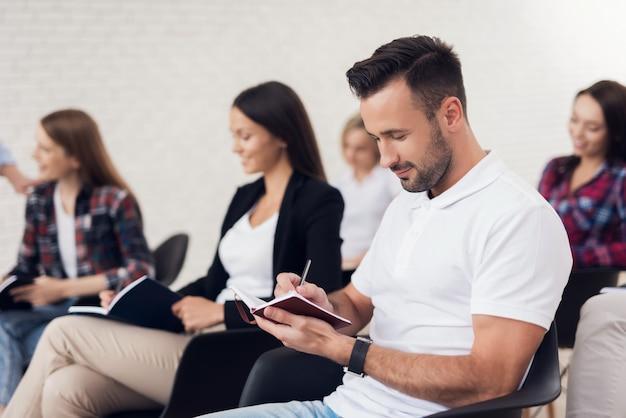 Mann macht notizen mit bleistift im notizbuch im publikum sitzen