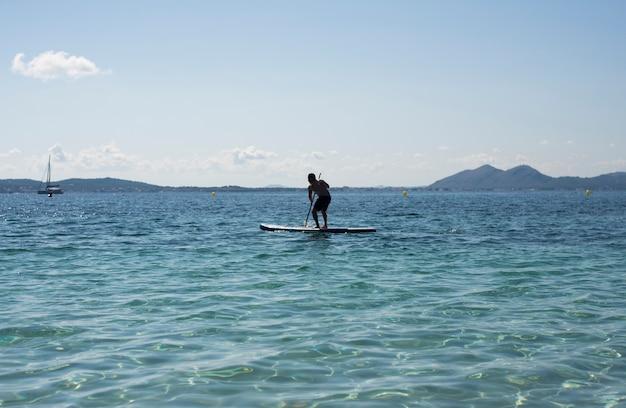 Mann macht paddle-surfen an einem paradiesischen strand im urlaub