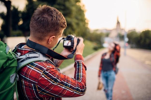 Mann macht schuss vor der kamera, frau posiert auf ausflug in touristenstadt. sommerwandern des liebespaares. wanderabenteuer von jungem mann und frau