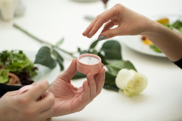 Mann macht seiner freundin einen heiratsantrag im restaurant, nahaufnahme