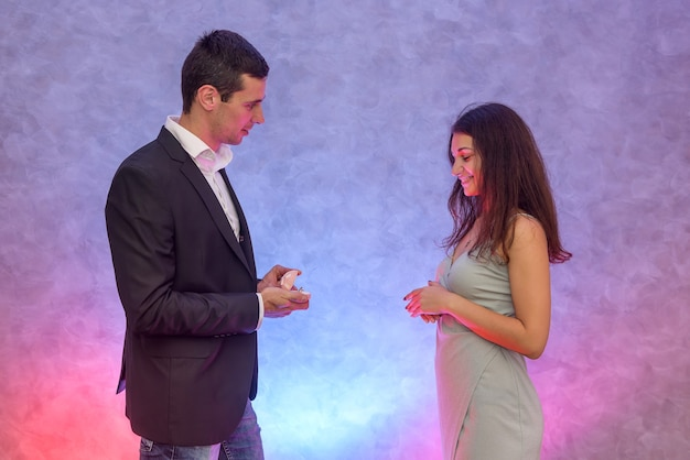Mann macht seiner freundin einen vorschlag und zeigt ihren goldenen ring mit diamant