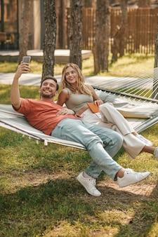 Mann macht selfie mit frau auf hängematte