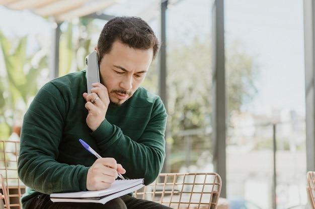 Mann macht sich beim telefonieren notizen