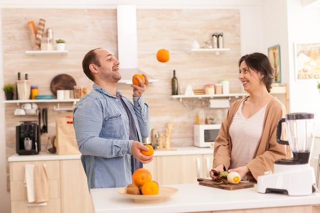 Mann macht tricks mit orangen für die frau in der küche, während er einen gesunden smoothie zubereitet. gesunder, unbeschwerter und fröhlicher lebensstil, ernährung und frühstückszubereitung am gemütlichen sonnigen morgen