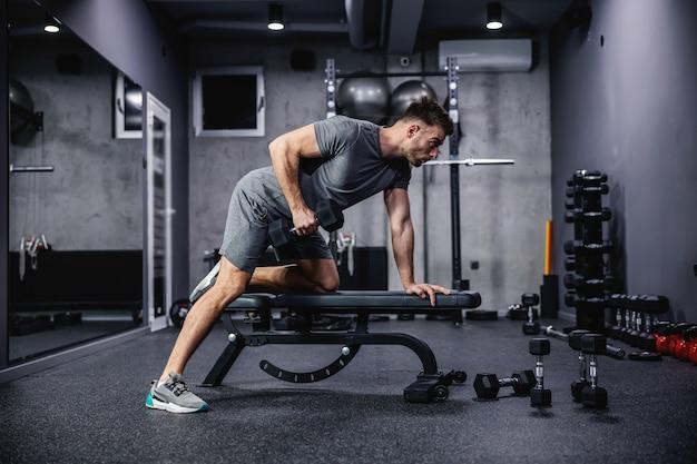 Mann macht übung mit hantel, die sich auf sportbank im fitnessstudio stützt. foto eines sexy muskulösen mannes in sportkleidung und gutem körperbau auf grauem hintergrund. kraft und motivation, sport, fitnessziel