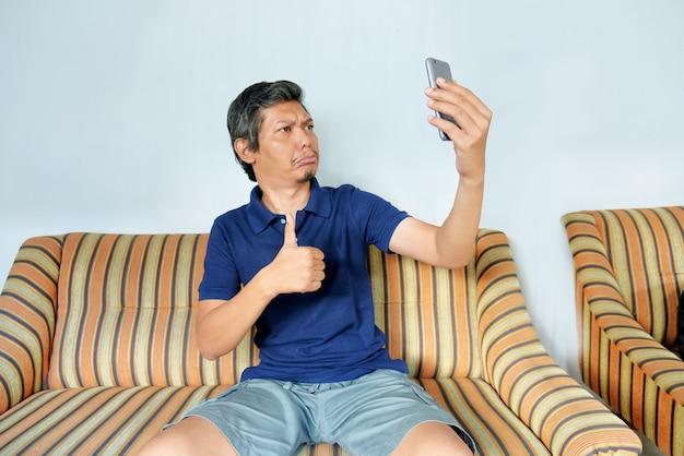 Mann macht videoanruf zu hause mit telefon