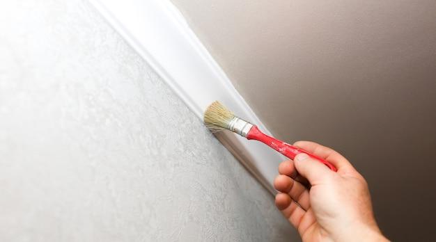 Mann malt gipsfußleiste mit pinsel an der decke. instandhaltungsarbeiten in der wohnung. restaurierung im innenbereich. trockenbauplatte.