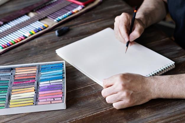 Mann malt mit bleistift und pastellkreide kreide auf papier