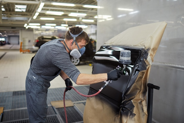 Mann malt teil vom auto, reparatur, tankstelle, autohaus