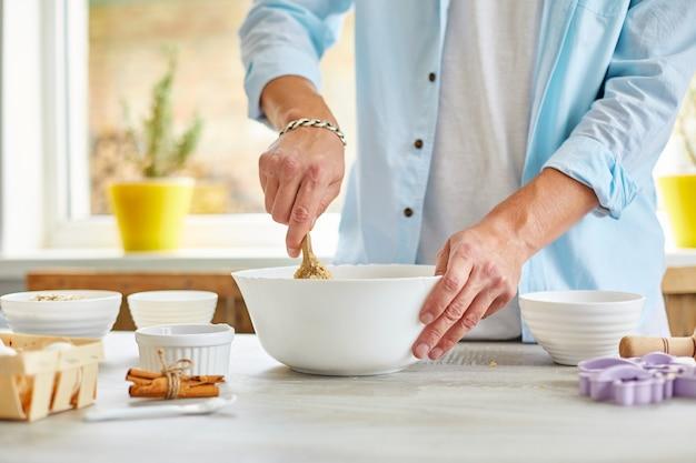 Mann, mann, der den teig in schüssel a bildet und zu hause in der küche knetet, vorbereitung für kekse, hausmannskost.