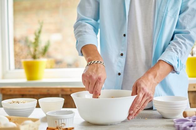 Mann, mann, der den teig in schüssel bildet und zu hause in der küche knetet, vorbereitung für kekse, hausmannskost.