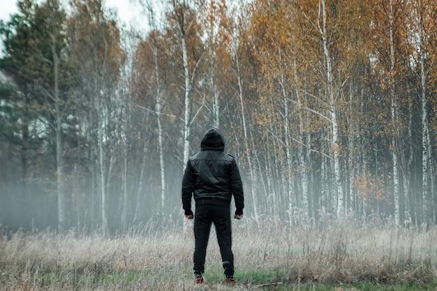 Mann, mann in einem schwarzen mantel bei nebel