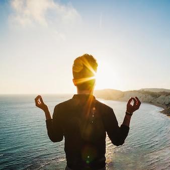 Mann meditiert auf klippe