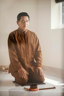 Mann meditiert mit klangschale und weihrauch