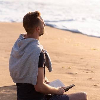 Mann meditiert neben dem meer