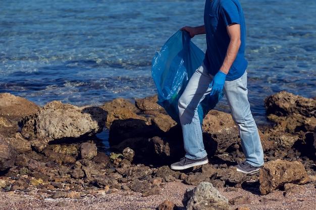 Mann meldet sich freiwillig mit großer tasche für müll, der müll am strand sammelt. konzept der umweltverschmutzung