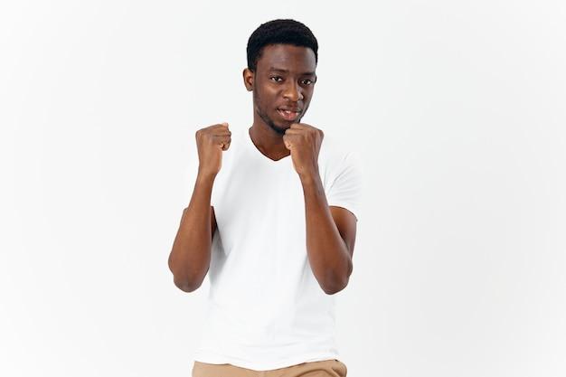 Mann mit afrikanischem aussehen im weißen t-shirt, der mit den händen gestikuliert, moderner lebensstil, zugeschnittene ansicht