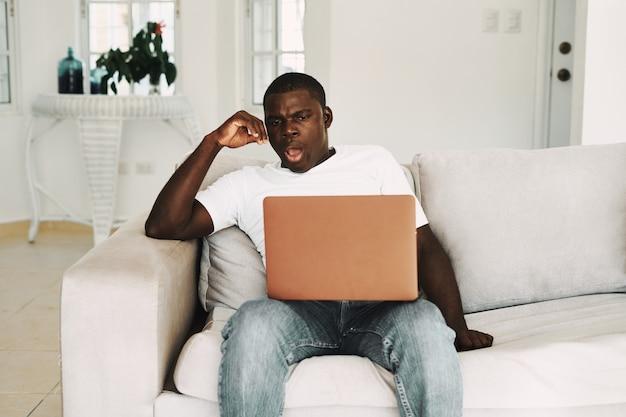 Mann mit afrikanischem aussehen sitzt auf der couch mit offenen laptops freiberufler, der außerhalb des büros arbeitet