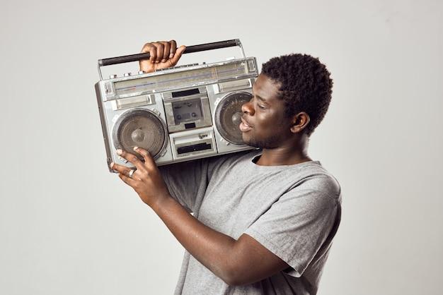 Mann mit afrikanischem aussehen tonbandgerät in händen musiknostalgie