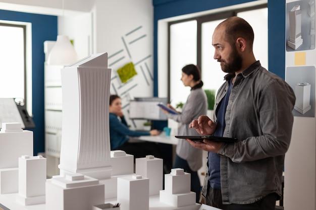 Mann mit architektenberuf, der im büro am bau von modelldesign-maquette auf dem tisch arbeitet. kaukasischer architektonischer baumeister, der ein projekt des industriebaus entwirft
