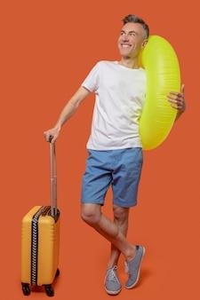 Mann mit aufblasbarem ring und koffer