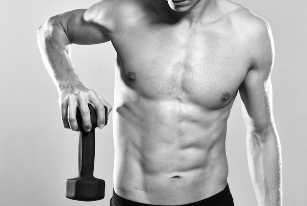 Mann mit aufgepumptem oberkörper trainiert muskeltraining posiert