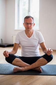 Mann mit augen schloss übendes yoga