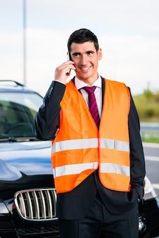 Mann mit autopanne abschleppdienst anrufend