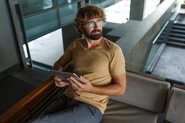 Mann mit bär, der tablette im modernen gebäude verwendet. auf dem sofa chillen.