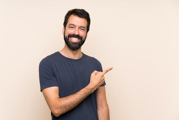Mann mit bart auf die seite zeigen, um ein produkt zu präsentieren