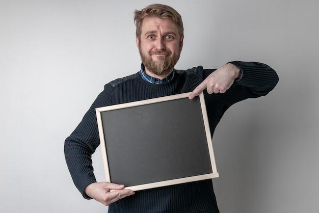 Mann mit bart, der auf leere tafel zeigt, erschrocken vor schock mit einem überraschungsgesicht, ängstlich und aufgeregt vor angstausdruck
