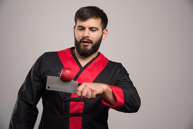 Mann mit bart, der auf roten apfel auf messer schaut.
