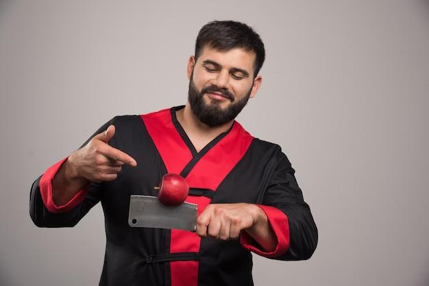Mann mit bart, der auf roten apfel auf messer zeigt.