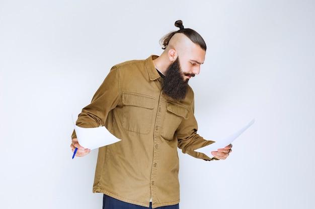 Mann mit bart, der die projektliste überprüft und notizen oder korrekturen markiert.