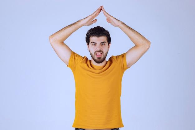 Mann mit bart, der ein dreieck oder ein dachzeichen zeigt
