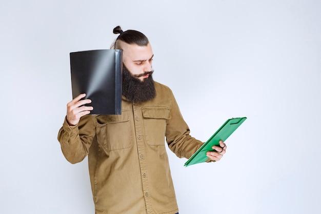 Mann mit bart, der ein quizpapier hält und verwirrt und nachdenklich aussieht.