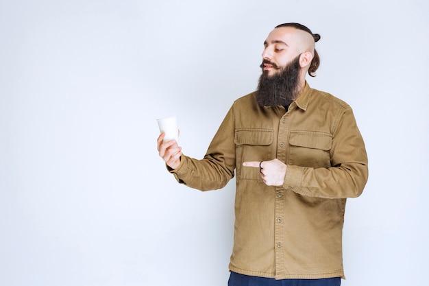 Mann mit bart, der eine tasse kaffee in einem einwegbecher hält.