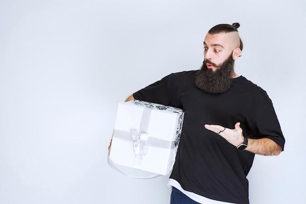 Mann mit bart, der eine weiß-blaue geschenkbox hält und enttäuscht aussieht.