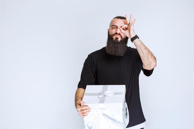 Mann mit bart, der eine weiß-blaue geschenkbox hält und über seine finger schaut.