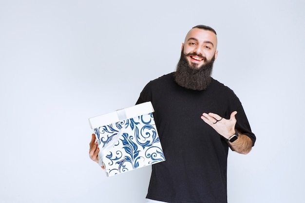 Mann mit bart, der eine weiße blaue geschenkbox hält und lächelt und sich glücklich fühlt.