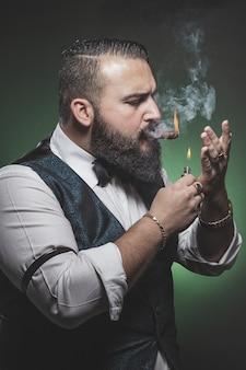 Mann mit bart, der eine zigarre anzündet.