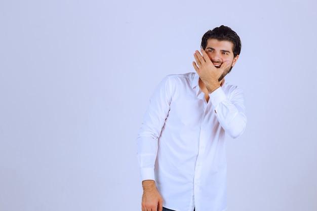 Mann mit bart, der einen teil seines gesichts bedeckt und lacht.