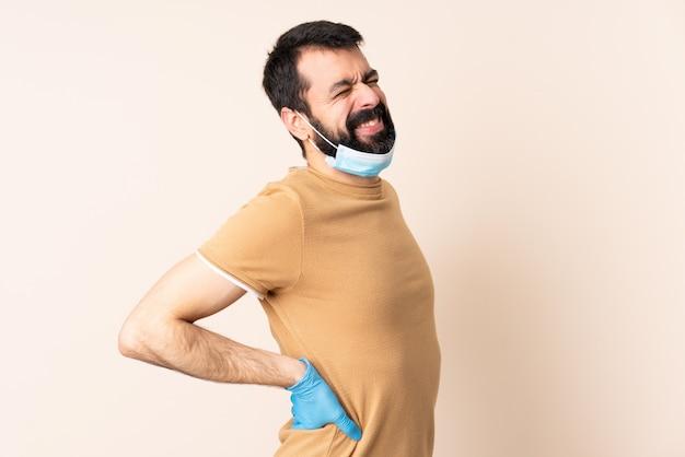 Mann mit bart, der mit einer maske und handschuhen über der isolierten wand vor dem coronavirus schützt und unter rückenschmerzen leidet, weil er sich bemüht hat