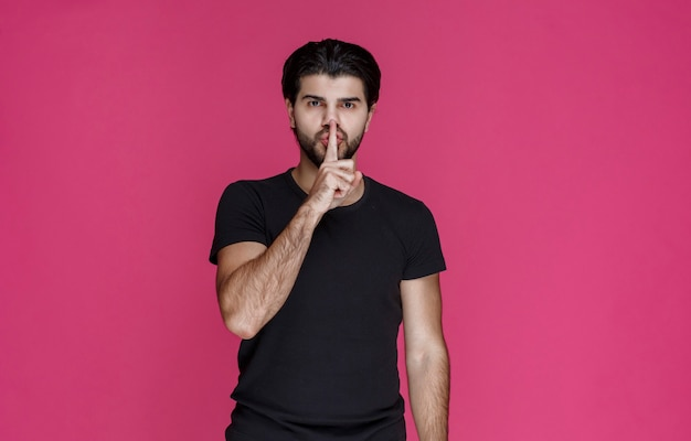 Mann mit bart, der schweigenzeichen macht oder hohes volumen zeigt